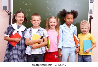 Image of curious schoolchildren standing by blackboard and looking at camera in the classroom