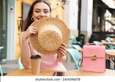 Image of cute brunette woman smiling and holding straw hat while sitting in street summer cafe with takeaway coffee