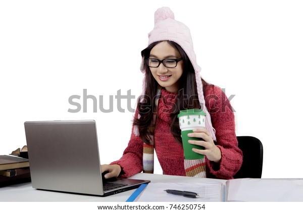 Image of cute female high school student studying with a laptop while holding a cup of hot chocolate