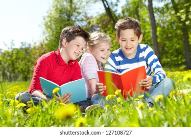 Image of cute friends reading on the lawn