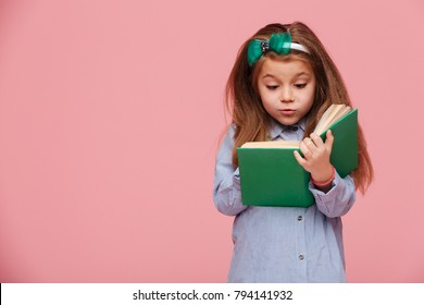 Image of cute girl 5-6 years with long auburn hair reading interesting book, being involved in education isolated over pink background