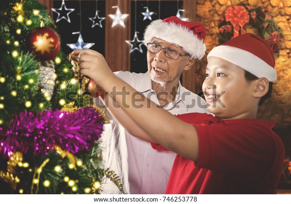 Image of a cute little boy with his grandfather putting an ornament ball on the Christmas tree. Shot at home