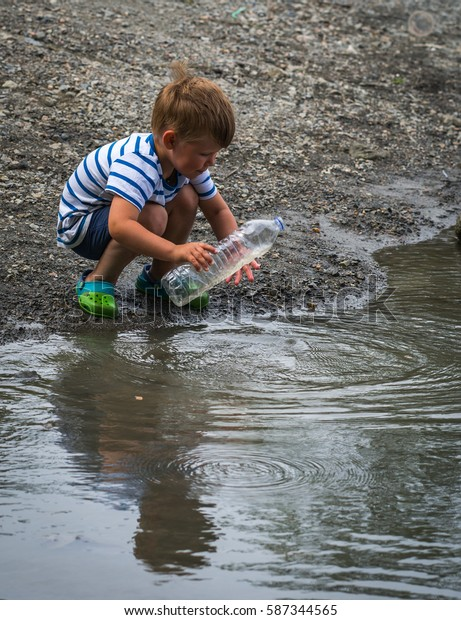Image of a cute little boy playing on the shore of the lake