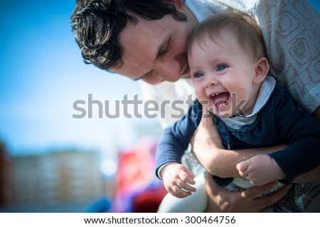 Image of cute little daughter in young dad's hands. Father and baby girl outdoor. Child plays on playground.