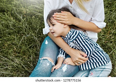 Image of cute little girl lying on her mother's legs outdoors. Loving mother and daughter sitting on the green grass in the park. Mom and kid cuddling and has fun. Good relationship. Mother's day