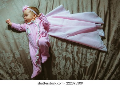 Image of cute little girl in pink suit and cloak indoor. Newborn baby, caucasian child. Super hero in her dreams.