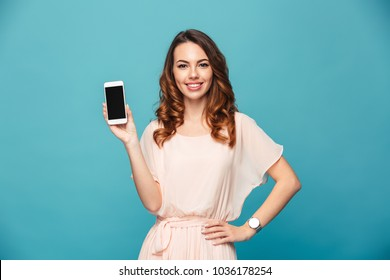 Image of cute pretty young lady isolated over blue background. Looking camera showing display of mobile phone.