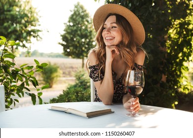 Image of cute pretty young woman sitting in cafe outdors in park with book holding glass drinking wine.