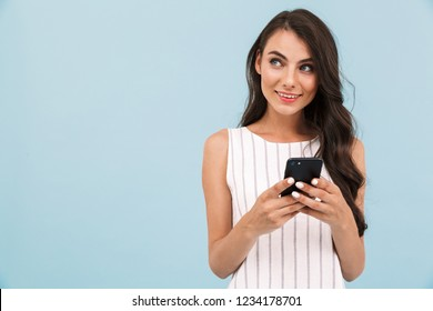Image of cute pretty young woman posing isolated over blue background wall using mobile phone.