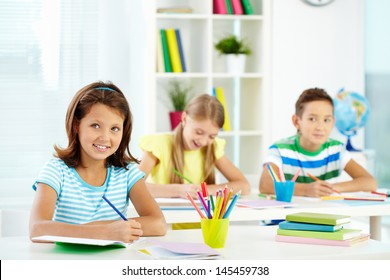 Image of cute school kids sitting at their workplaces and doing the tasks