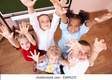 Image of cute schoolchildren looking at camera and laughing with their arms raised