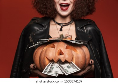 Image of cute witch girl in halloween costume holding carved pumpkin with cash money isolated over red wall