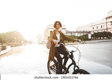 Image of a cute young amazing woman walking outdoors in park with bicycle beautiful spring day.