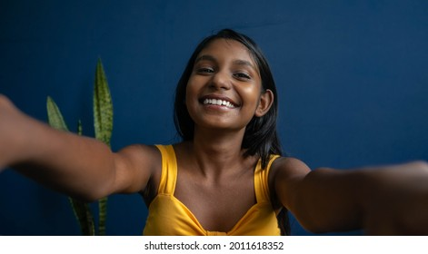Image of a cute young brunette teenage girl  reaching hands forward catching something | smiling girl with friendly expression trying to greet someone with a warm hug