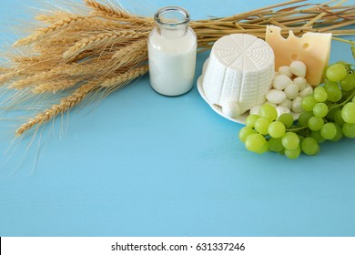 image of dairy products and fruits on wooden background. Symbols of jewish holiday - Shavuot