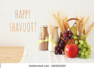 image of dairy products and fruits over wooden background. Symbols of jewish holiday - Shavuot