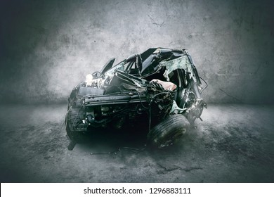 Image of damaged black car after colliding in the studio with wall background