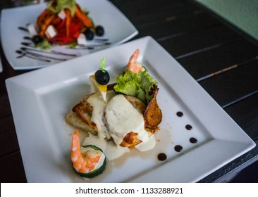Image of decorated fish with seasonings, sauce and cheese on a white square plate. selective focus