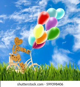 Image of decorative little man on a bicycle, balloon  against the sky.Wooden man and balloons as a symbol of love and a holiday mood.