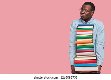 Image of dejected black man looks with miserable expression aside, holds pile of books, dressed in formal clothes, learns much information for coming examination, models over pink wall with free space