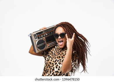 Image of delighted african american woman smiling and holding vintage boombox with cassette tape on her shoulder isolated against white background