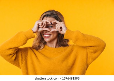 Image of delighted blonde woman in warm sweater laughing and showing heart shape isolated over yellow background