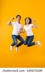 Image of delighted multinational couple making winner gesture while jumping isolated over yellow background