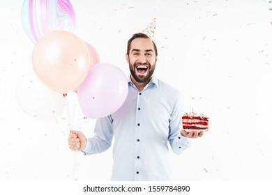 Image of delighted party man laughing and holding birthday cake with air balloons isolated over white background