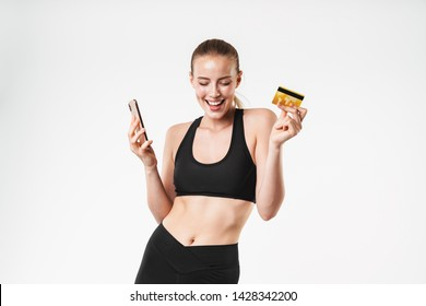 Image of delighted sporty woman wearing tracksuit rejoicing while holding credit card and cellphone isolated over white wall