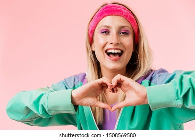 Image of delighted young woman in green jacket showing heart shape with fingers isolated over pink background