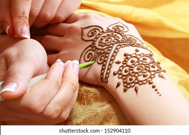 Image detail of henna being applied to hand over golden fabric
