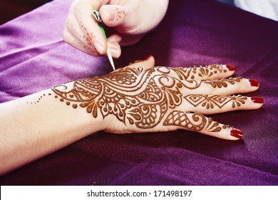 Image detail of henna being applied to hand close up