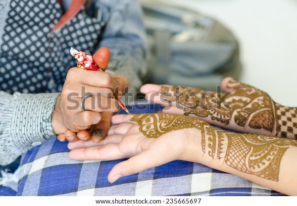 Image detail of henna being applied to hand.