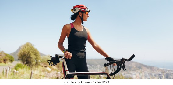 Image of determined female cyclist looking away. Fit woman wearing sportswear and cycling helmet looking at copyspace.