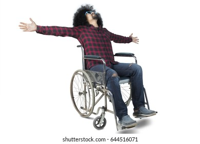 Image of disabled Afro man sitting on a wheelchair while raising hands, isolated on white background