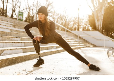 Image of disabled athletic girl in sportswear doing sit ups and stretching bionic leg at stairs outdoors