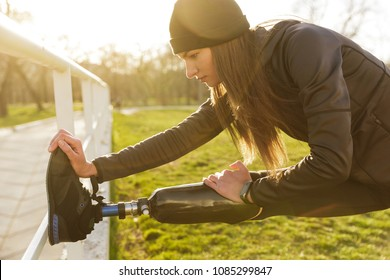 Image of disabled running woman in sportswear doing slopes and stretching prosthetic leg on grass using railing