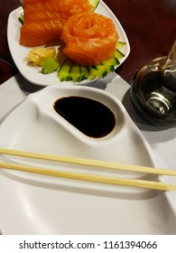 Image of dish with soy sauce and hashi in the background image of slices of salmon or sushi