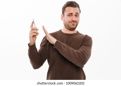 Image of displeased confused young man standing isolated over white background talking by mobile phone. Looking camera.