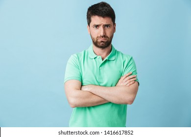 Image of a displeased young handsome bearded man posing isolated over blue wall background.