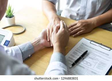 Image of doctor holding patient's hand to encourage, talking with patient cheering and support.