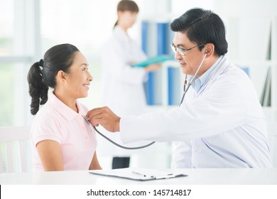 Image of a doctor listening to a senior woman's chest