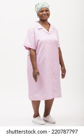 image of a domestic worker in her work uniform standing with her hands at her sides and smiling