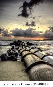 image of drain pipe on the coast. waves and dramatic cloud during the sunset sunrise. hidden sunlight behind the cloud