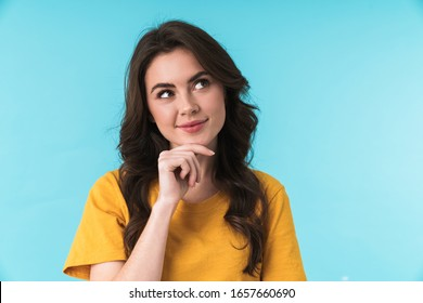 Image of a dreaming pleased young pretty woman posing isolated over blue wall background.
