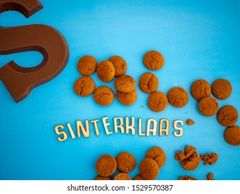 Image for the Dutch fest of Sinterklaas with candy called pepernoten and a chocolate letter. On a blue background. The Dutch word Sinterklaas (meaning Santa Claus) is spelled in wooden letters.