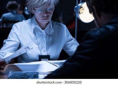 Image of elder policewoman examining a suspected man