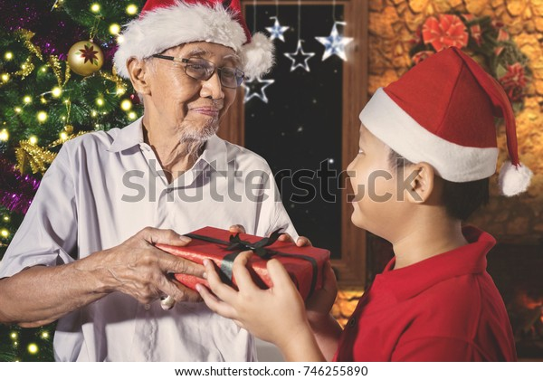 Image of an elderly man with expression happy while receiving a Christmas gift from his grandson. Shot at home
