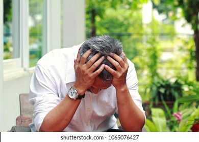 Image of elderly stresness man facepalm or cover his face by hands.4os or 50s man depressed,or may suffering from headaches and migraine as of Menopause in men,get trouble in his life