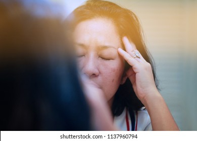 Image of elderly stressed woman in the mirror.She facepalm or cover her face by hand.4os Aain woman depressed,or may suffering from headaches and migraine as of Menopause or get trouble in her life